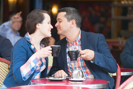 Couple in a Parisian street cafe, drinking coffee photo