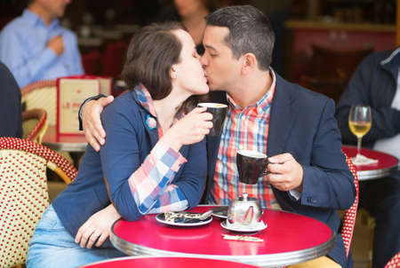 Couple in a Parisian street cafe, drinking coffee and kissing photo