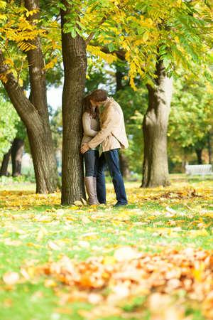 romance: Casal se beijando no parque em um dia de outono Imagens
