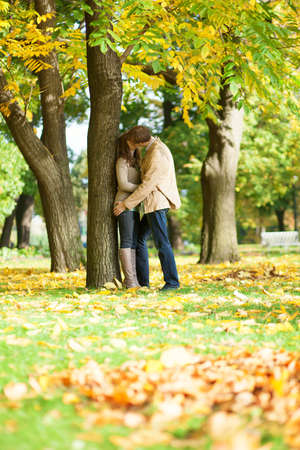 september 2: Couple kissing in park on a fall day