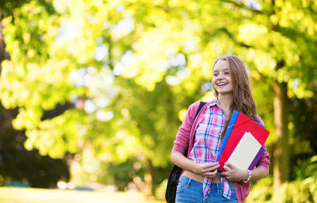 Student girl outdoors going back to school and smiling photo