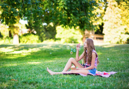 Young girl sitting on the grass and blowing bubbles photo