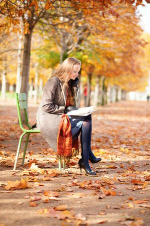 Menina lendo um livro no parque Banco de Imagens