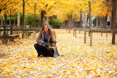 autumn city: Beautiful girl gathering autumn leaves in park Stock Photo