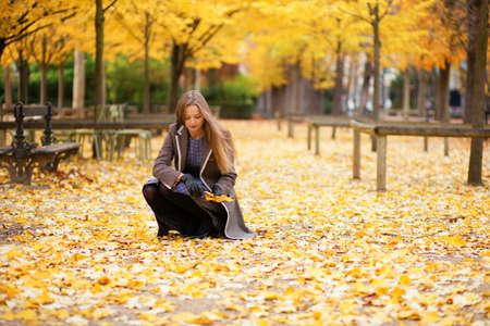 Mooi meisje verzamelen van herfstbladeren in het park