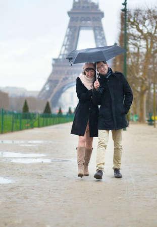 la tour eiffel: Dating couple under the rain in Paris Stock Photo