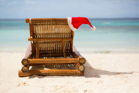 Santa hat on chaise longue on white sand beach Stock Photo