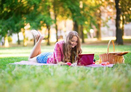 net surfing: Ragazza che ha un picnic e navigazione in rete