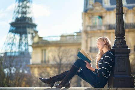 Mulher nova bonita em Paris, lendo um livro Banco de Imagens