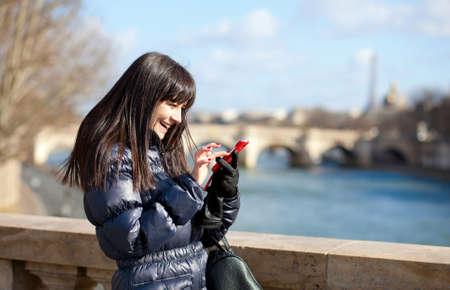Happy beautiful brunette tourist in Paris sending an sms photo