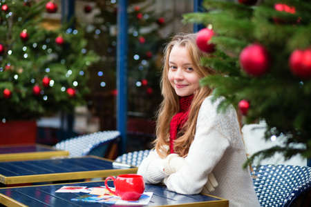 Smiling girl with greeting cards in a Parisian cafe photo