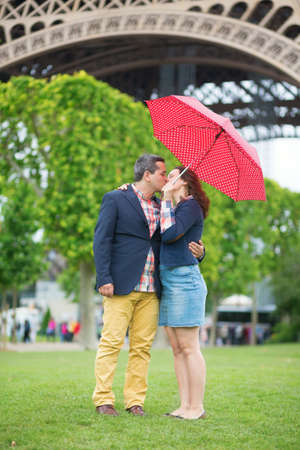 Couple under red umbrella near the Eiffel tower photo