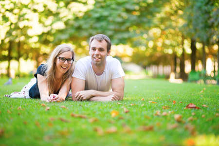 Happy smiling couple lying on the grass