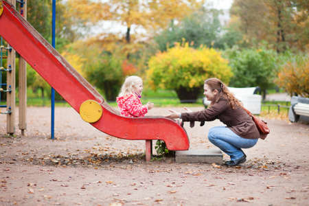 Mother and daughter having fun together on playground photo