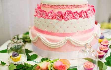 Wedding cake decorated with pink roses photo