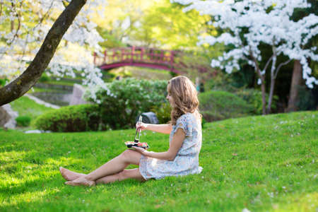 Young woman eating sushi in Japanese park photo