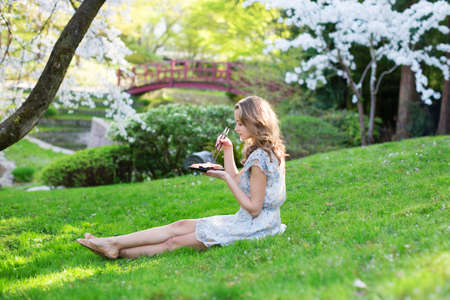 Young European woman eating sushi in Japanese park photo