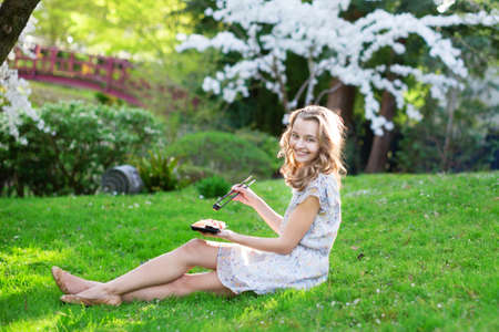 Young European woman eating sushi in Japanese park. photo