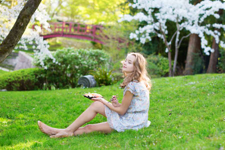 Young woman eating sushi in Japanese park. photo