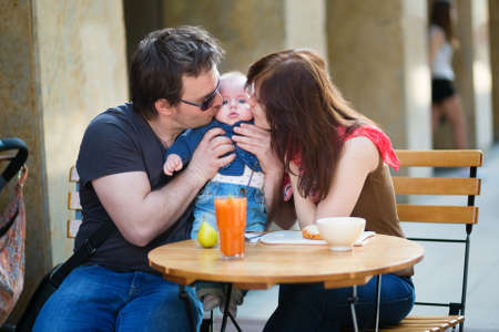 Happy family of three having breakfast in a cafe photo