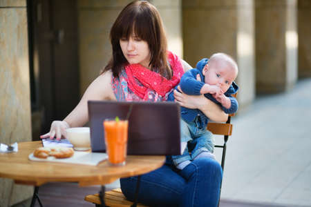 Young mother with little son working on her laptop in a cafe photo