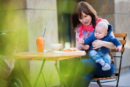 Young mother with her little son having breakfast in a cafe photo