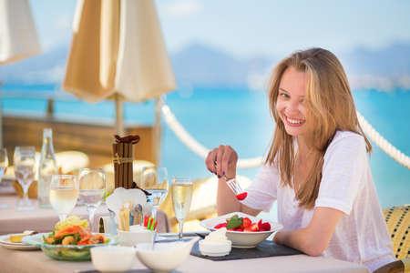 eating fruits: Joven y bella mujer de comer frutas en un restaurante de la playa Foto de archivo