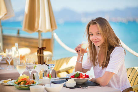 Beautiful young woman drinking champagne in a beach restaurant photo