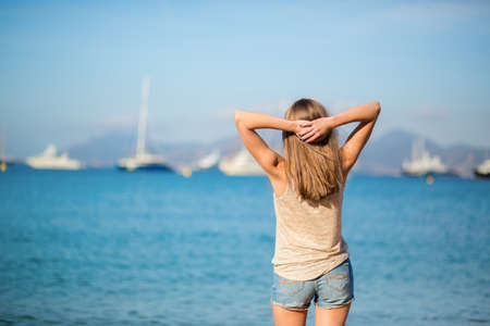 Young girl relaxing near the sea and enjoying her vacation photo