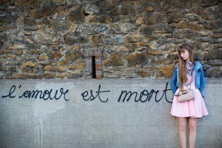 splitting up: Sad girl near the wall Love is dead in French is written
