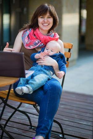 werkende moeder: Jonge werkende moeder met haar zoontje in een cafe Stockfoto