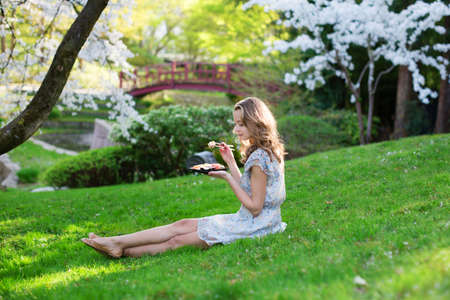 Young European woman eating sushi in Japanese style park photo