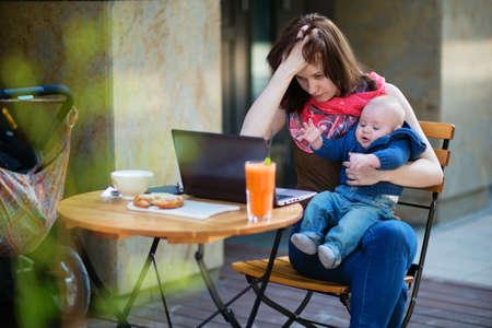 피곤 젊은 어머니 오 그녀의 노트북을 작동 4 개월 아들 들고