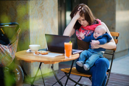 stressed: Tired young mother working oh her laptop and holding 4-month son