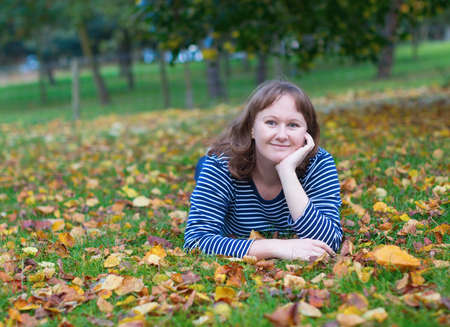 jardin de luxembourg: Happy girl lying on the ground covered with fall leaves