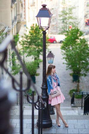 streetlamp: Beautiful girl in pink dress on Montmartre in Paris