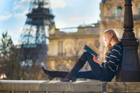 Mooie jonge vrouw in Parijs, het lezen van een boek