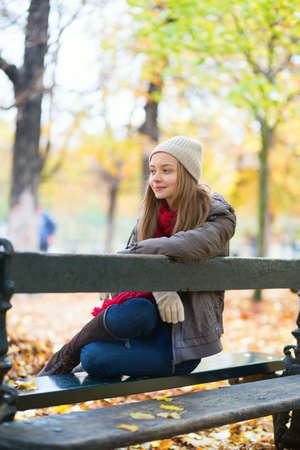Young girl sitting on a bench in park on a fall day Stock Photo - 30082025