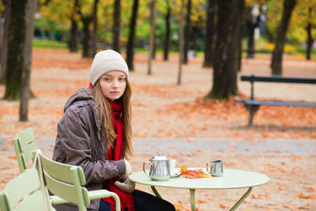 Girl drinking coffee in an outdoor Parisian cafe on a fall day Stock Photo - 30082028