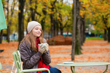 Girl drinking coffee in an outdoor Parisian cafe on a fall day Stock Photo - 30082030
