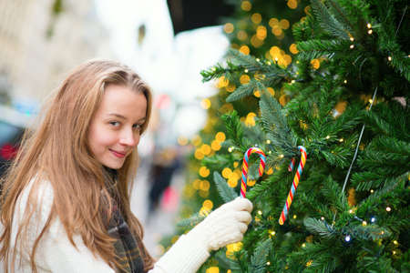 decorating christmas tree: Girl decorating Christmas tree with colorful candies Stock Photo