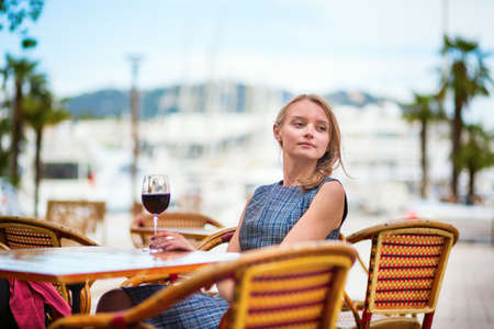 french riviera: Young French woman drinking red wine in an outdoor cafe of Cannes