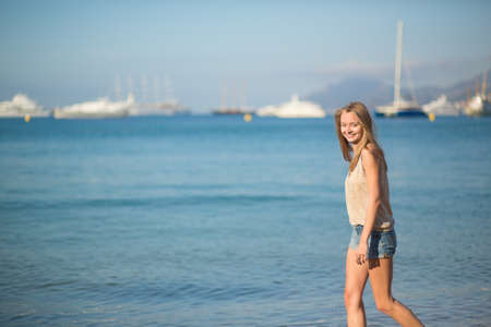 Beautiful young girl walking on the beach in Cannes, France photo