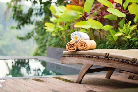 spas: Handtücher mit weißen Frangipani-Blüten in einem balinesischen Spa