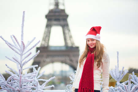 Girl in Santa hat near the Eiffel tower in Paris during Christmas time photo
