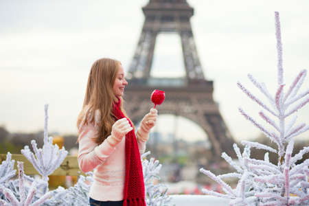 Girl with caramel apple on a Parisian Christmas market photo