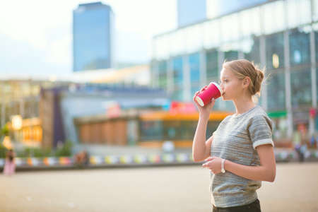 Girl drinking coffee at La Defense, business district of Paris photo