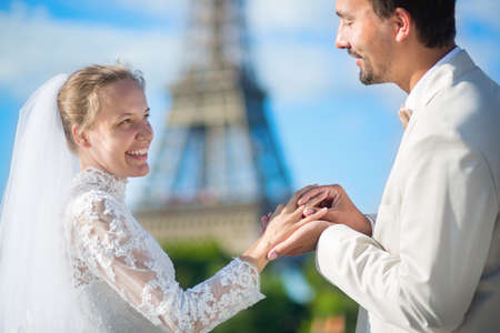 Groom putting wedding ring on a finger of his bride photo