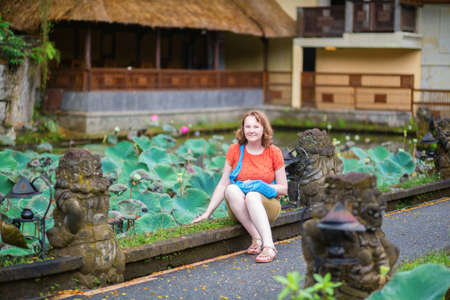saraswati: European tourist sitting near lotus pond Lotus pond in Pura Saraswati temple in Ubud, Bali
