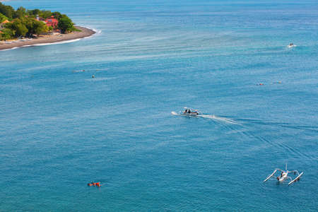 People snorkeling in turquoise water on the Eastern coast of Bali photo